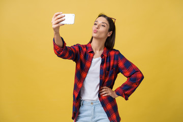 Portrait of a smiling woman making selfie photo on smartphone isolated on a yellow background