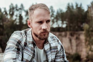 Good-looking dark-eyed man wearing squared shirt sitting outside enjoying fresh air