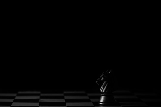 black horse chess on a chessboard in the dark background. - Business leader concept.