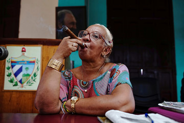 """Tobacco """"fabric reader"""" Grisel Valdez smokes a cigar during a break at the H. Upmann tobacco factory in Havana"""