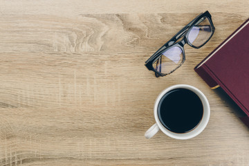 a cup of coffee and an eyeglasses with a red book on the wooden table.