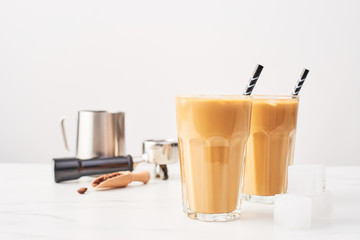 Barista concept. Ice coffee in a tall glass with straws and milk pitcher, portafilter and wooden coffee measure on white marble table over white background. Selective focus and copy space.