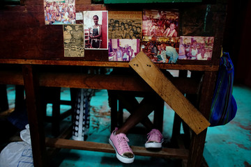 "Ines Drake has pictures of her displayed at her working station as she rolls tobacco listening to ""fabric reader"" Odalis de la Caridad at the Corona tobacco factory in Havana"