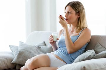 Beautiful young woman eating yogurt at home.