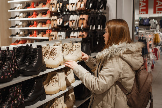 Young woman in beige winter clothes choosing trendy beige winter boots in the mall