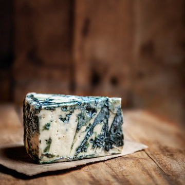 Blue cheese Gorgonzola on a rustic wooden background. Mold cheese with copyspace and dark backdrop.