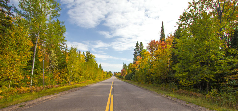 Scenic Fall Color Tour Panorama. Open road to the horizon framed in fall foliage in the Upper Peninsula of Michigan.