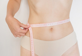 Slim young woman measuring her thin waist with a tape measure, fitness and diet concept