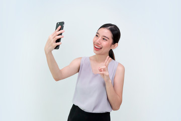 Asian Business girl having video-call with lover holding smart phone in hand shooting selfie