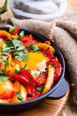 Shakshuka, fried eggs cooked in tomatoes and bell peppers sauce