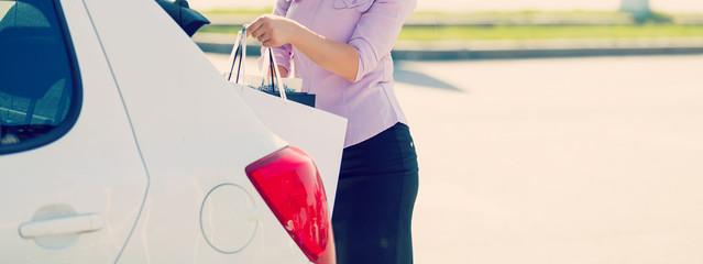 young beautiful women open car's door.beautiful girl with shopping bags near a her car.shopping