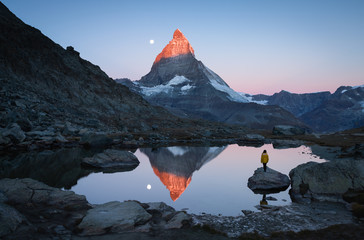 Fotomurales - A girl on a rock in the Riffelsee watching the first sunlight shining on the Matterhorn.