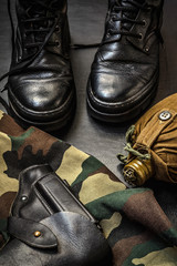 set of military uniforms, shoes, a flask, a weapon gun on a dark background