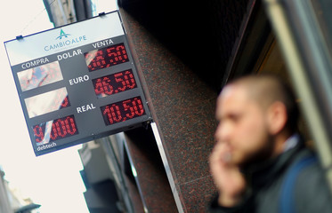 A man talks on his cellphone next to a currency exchange board in Buenos Aires' financial district