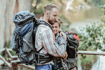 Break in hiking. Loving handsome bearded backpacker hugging his appealing young woman while making break in hiking