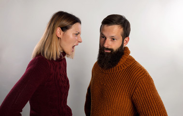 Angry woman screaming against her husband both dressed in warm knitted sweaters. Isolated gray background