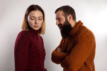 Young bearded man screaming against a sad young woman both dressed in warm knitted sweaters. Isolated gray background