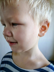 Unhappy little boy blond hurt his lip and crying with tears.