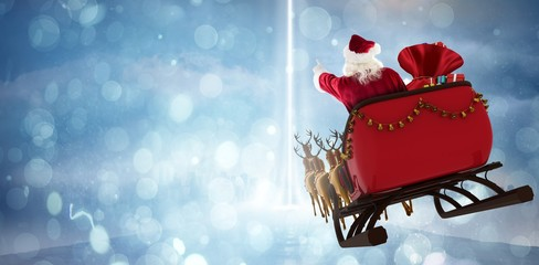 Composite image of santa claus riding on sled with gift box Wall mural
