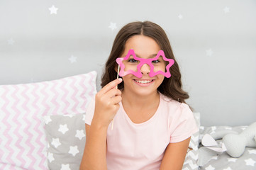 Slumber party photo booth props. Kid girl cheerful posing with star shaped eyeglasses party attribute. Prepare photo booth props hand made or buy for party. Printable photo booth props pajama party