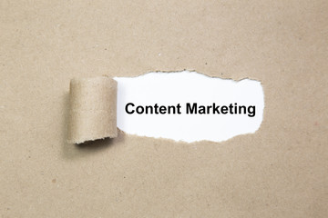 Content Marketing text on paper. Word Content Marketing on torn paper. Concept Image.