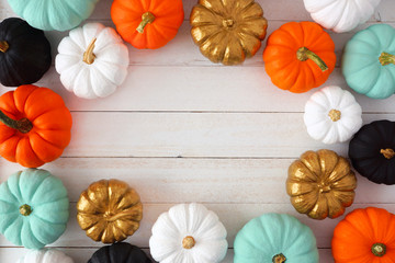 Autumn frame of various colorful pumpkins on a white wood background. Top view with copy space.