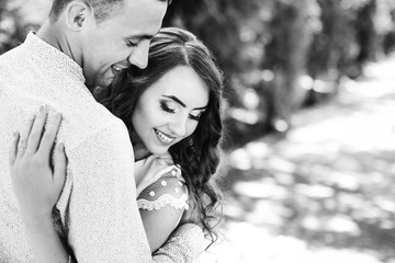 The guy hugs a girl with a beautiful hairstyle and gentle makeup that closes her eyes and they enjoy each other on a black and white photo