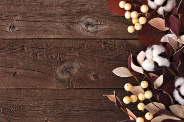 Side border of red leaves and berries over a rustic wood background. Top view with copy space.