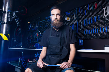 Portrait of small business owner of young man with beard. Guy bicycle mechanic workshop worker sitting with tool in his hand in a working black clothes in an apron in the background of a bicycle shop.