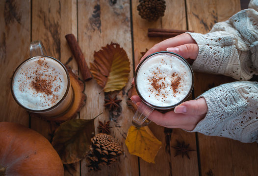 Hands holding pumpkin spice latte in glass cup on wooden background
