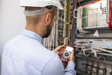 Young adult electrician builder engineer inspecting electric equipment in distribution fuse box. Electrical engineer worker in control panel. Maintenance electro box with multimeter