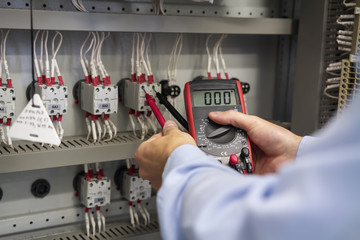 Multimeter in hands of electrician closeup. Service works in electrical box. Maintenance of electric panel. Technician testing voltage fuse box. Worker with tester