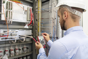 electrician technician in fuse box. Maintenance engineer in control panel. Worker is testing automation equipment. Engineering in electrical station. Electric man with multimeter in hands. Service.