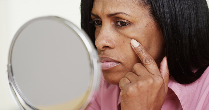 Closeup of black middle aged woman looking into mirror