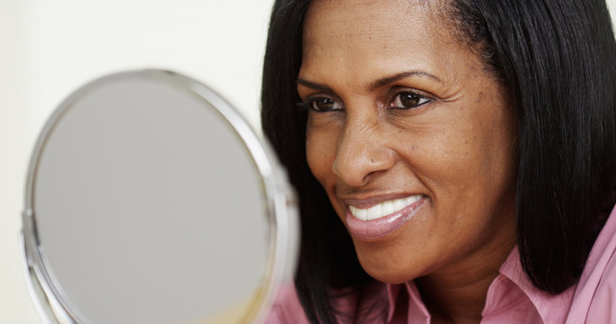 Portrait of African American woman smiling at a mirror