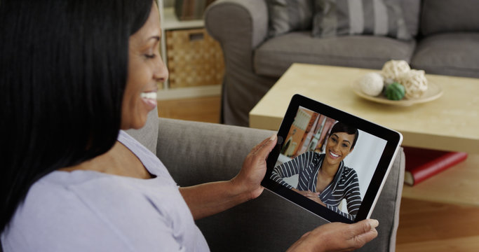 Happy Black woman talking to friend on tablet