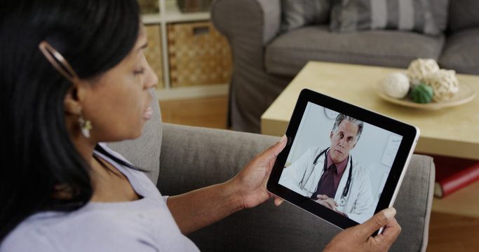 Middle aged Black woman consulting doctor on tablet