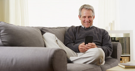Happy middle-aged white man texting on a cell phone