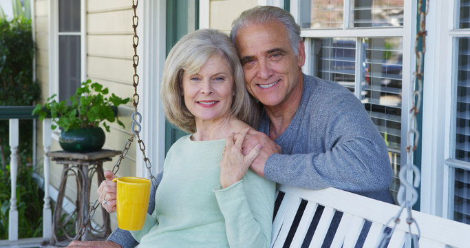 Elderly couple smiling on porch looking at camera