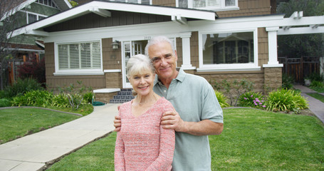 Senior couple standing smiling in front of new home Wall mural
