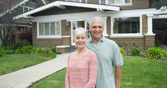 Senior couple standing smiling in front of new home