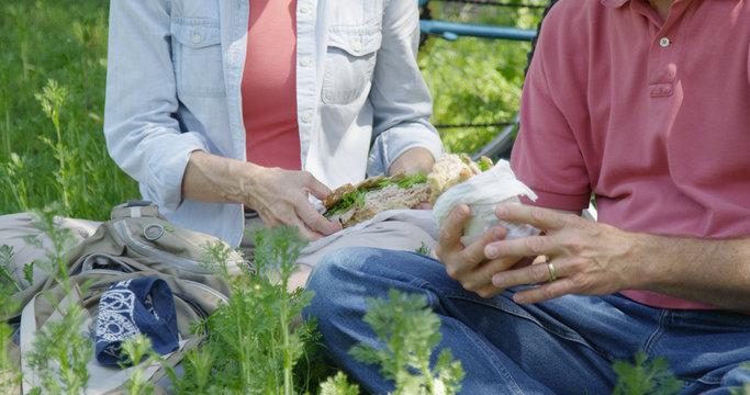 Elderly white couple taking lunch break from hike