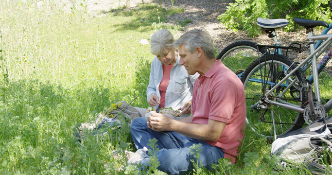 Mature caucasian couple eating sandwich at a park