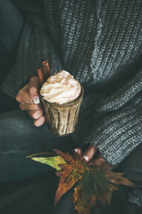 Woman in grey woolen sweater and jeans sitting and holding mug with hot chocolate or coffee with whipped cream and cinnamon and fallen leaves in hands. Fall warming sweet drink