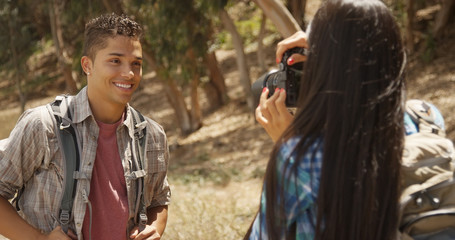 Happy young backpacker girlfriend taking pictures of boyfriend on hiking trail