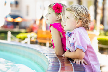 Cute Young Caucasian Brother and Sister Enjoying The Fountain At The Park