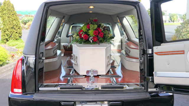 closeup shot of a funeral casket in a hearse or chapel or burial at cemetery