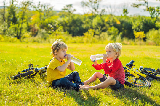 Two little boys drink water in the park after riding a bike