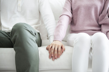 ソファで、手を繋ぐカップル。手のアップ。 Wall mural