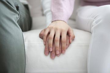 ソファで、手を繋ぐカップル。手のアップ。